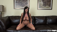 Busty brunette Milf babe Lisa Ann is on the couch posing and showing off