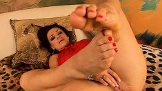 Seductive redhead displays her lovely feet and pleases her fiery twat