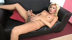 Blonde ladyboy spreads her body across the couch and strokes her cock