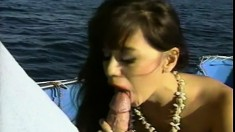 Desirable brunette worships a cock and gets banged in the ass on a boat
